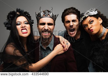 Multiethnic Friends In Scary Halloween Costumes Grimacing At Camera Isolated On Grey