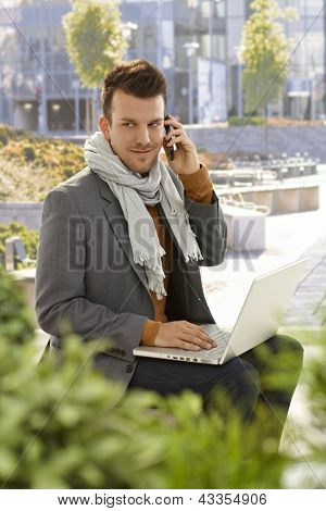 Young businessman sitting in citypark, talking on mobilephone, using laptop computer. poster