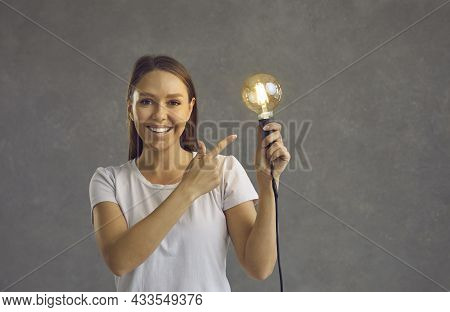 Happy Beautiful Woman Holding Light Bulb Suggesting Good Idea And Smart Solution To Problem