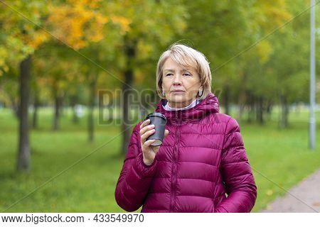Portrait Of An Adult Pretty Woman In A Bright Burgundy Jacket With A Disposable Cup Of Coffee In Her