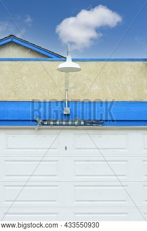 SUNSET BEACH, CALIFORNIA - 13 MAY 2021: Urban detail. Barracuda and lamp over garage door, with blue sky and single cloud.