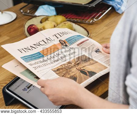Paris, France - Aug 12, 2021: Side View Of Woman Reading In The Kitchen Early In The Morning Financi