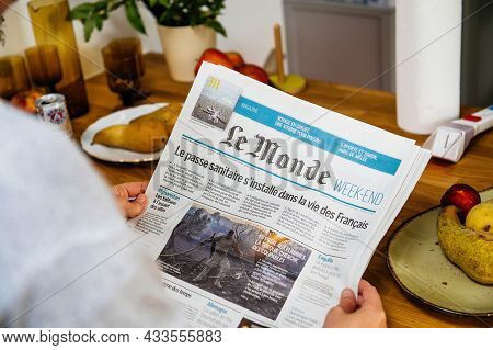 Paris, France - Aug 12, 2021: Woman Reading In The Kitchen Early In The Morning Le Monde Newspaper M