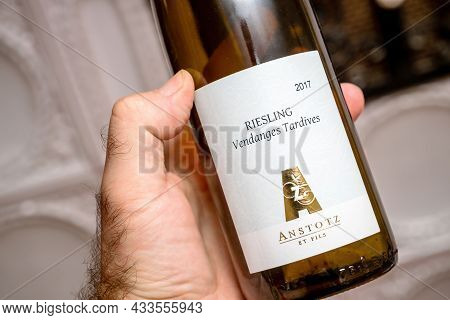 Paris, France - Sep 8, 2021: Rear View Of Male Hand Reading Holding Alsace Anstotz Et Fils Riesling