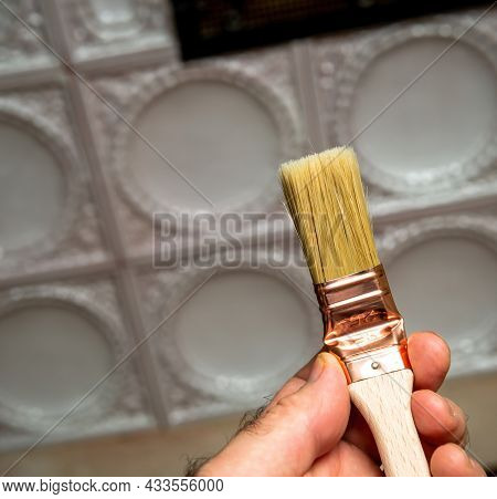 Male Hand Holding New Paintbrush For House Home Decoration And Painting With Vintage Stove In Backgr