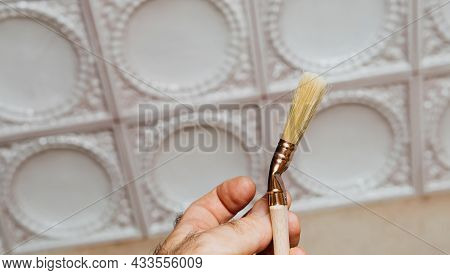 Male Hand Holding New Natural Paintbrush For House Home Decoration And Painting With Vintage Stove I