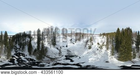 360 degree panoramic aerial view waterfall on small mountain river in winter forest with snow-covered trees