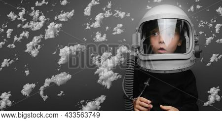 Small child wants to fly an airplane wearing an airplane helmet flying in the clouds