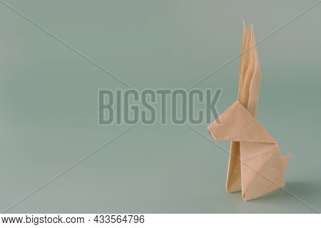 Paper Origami Bunny On A Blue Pastel Background. Crafts Made Of Paper. The Minimal Concept Of Easter