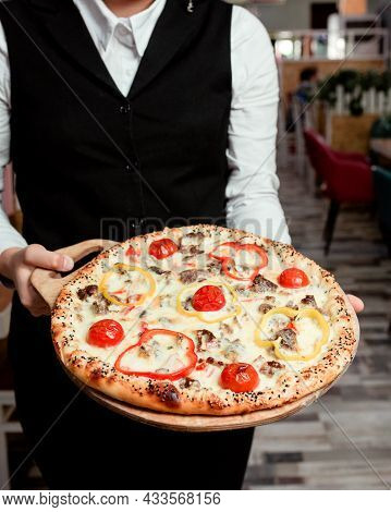 Waiter Holds Meat Pizza With Yellow Red Bell Peppers Tomato And Cheese