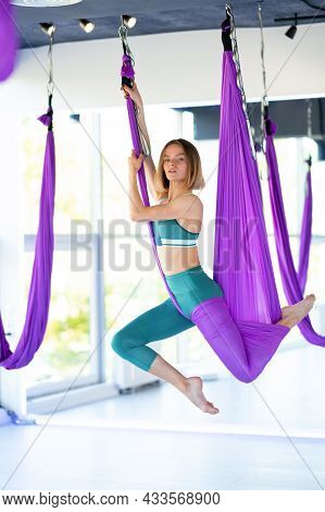 Young Smiling Woman Practice In Aero Stretching Swing. Aerial Flying Yoga Exercises Practice In Purp