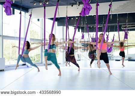 Group Of Young Women Practice In Aero Stretching Swing. Aerial Flying Yoga Exercises Practice In Pur
