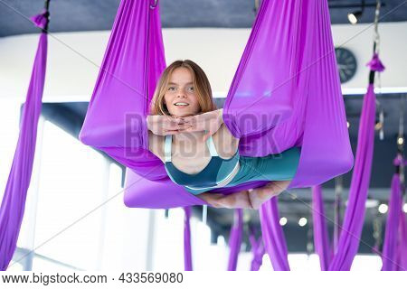 Portrait Young Smiling Woman Practice In Aero Stretching Swing. Aerial Flying Yoga Exercises Practic
