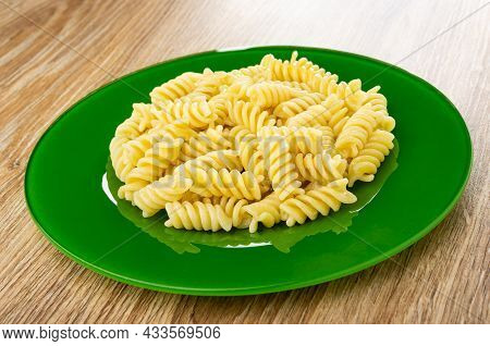 Boiled Pasta Fusilli In Green Glass Plate On Wooden Table