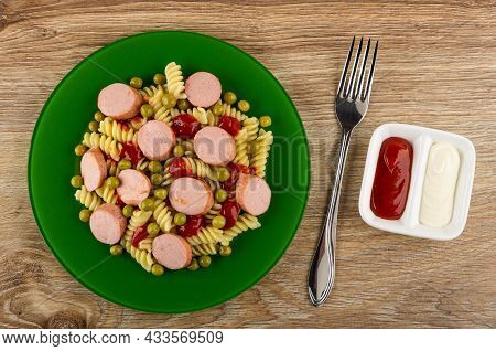 Green Glass Plate With Boiled Pasta Fusilli, Fried Sausages And Tomato Sauce, Fork, Partitioned Sauc