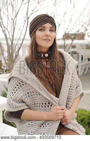Beautiful brunette woman portrait, looking at camera, dressed in jersey turban, autumn fashion