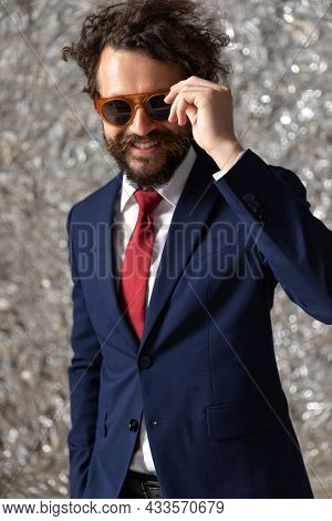 sexy businessman arranging his sunglasses and smiling at the camera on staniol background
