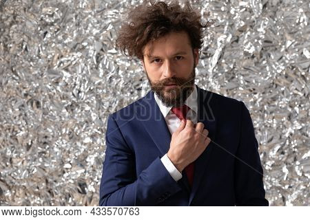 handsome businessman arranging his tie and looking at the camera with attitude on staniol background