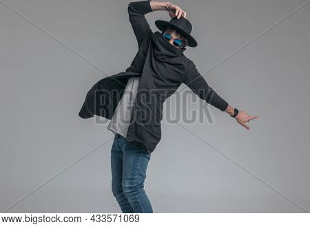 fashion model hiding his face in his cardigan's collar, adjusting his hat and posing with attitude