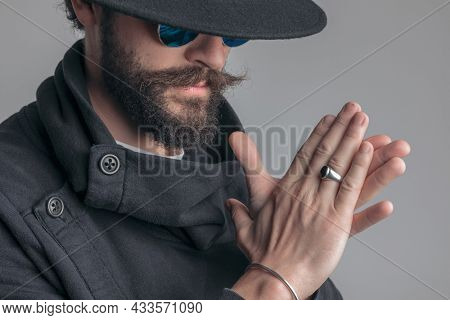 close up on a casual mysterious man rubbing his palms with tough attitude on gray background