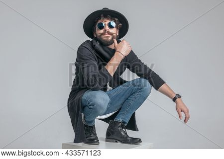 cool squatted casual man touching his face and having a tough attitude against gray background