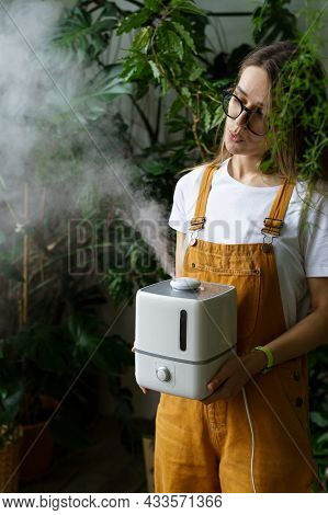 Young Gardener Woman Use Electric Humidifier Device To Keep Humidity Indoors During Heating Season C