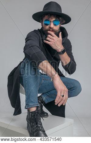 sexy casual man with tough attitude is touching his face and squatting against gray background