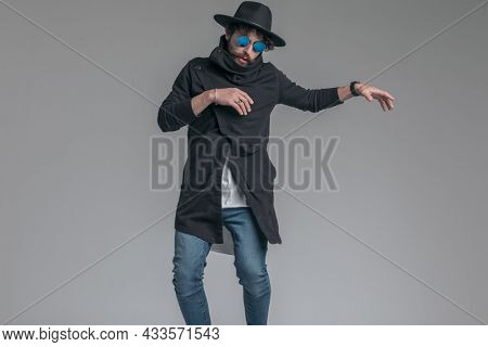 young casual man posing with his arms loose and wearing a hat and sunglasses on gray background