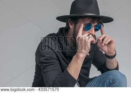 cool hipster with attitude is fixing his sunglasses, wearing a hat and squatting on gray background