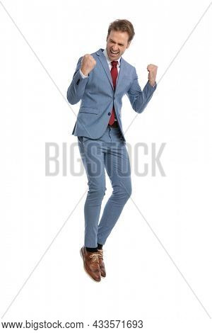excited elegant man in blue suit holding fists in the air, celebrating victory and jumping in the air, laughing and shouting on white background in studio