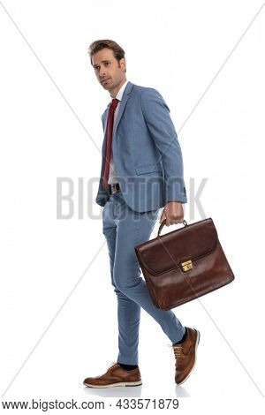 side view of sexy elegant businessman in blue suit looking to side, holding bag and walking in front of white background in studio