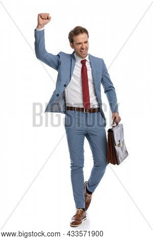 enthusiastic young guy holding fist up, holding suitcase, laughing and screaming while celebrating victory and walking in front of white background in studio