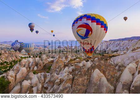 Cappadocia, Turkey - August 31, 2011: Hot air balloon flying over rocky landscape at sunrise in Cappadocia.
