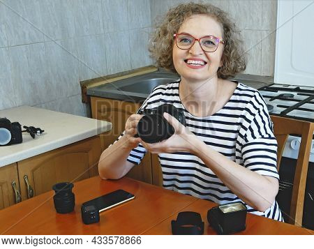 Woman Photographer Making Her Blog About Photo And Video Camera In Kitchen, Lens And Flash Equipment