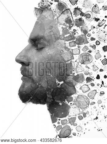 Paintography. A profile portrait of a man with closed eyes combined with watercolor splashes in a double exposure technique.