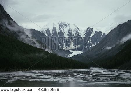 Atmospheric Alpine Landscape With Mountain Streams From Snowy Mountains In Overcast Weather. Bleak M