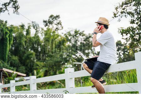 Asian Young Man Traveler Using Laptop Computer While Enjoying Beautiful Tropical In Nature. Freelanc