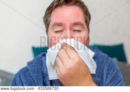 Healthcare, People And Medicine Concept - Ill Man Blowing Nose At Home. Sick Male At Home Have Healt