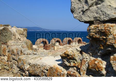 The Dilapidated Walls Of An Ancient Building With Arches Overlooking The Sea. A View Of The Sea From