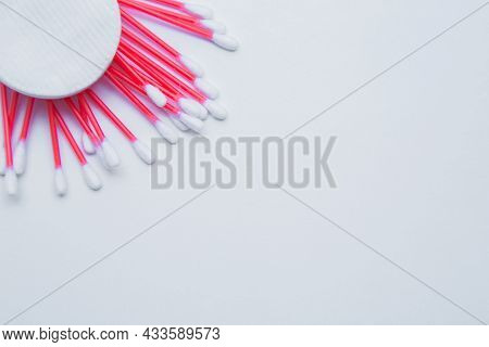 Disposable Ear Sticks With A Red Wand And White Disposable Cotton Sponges Lie On A White Background.