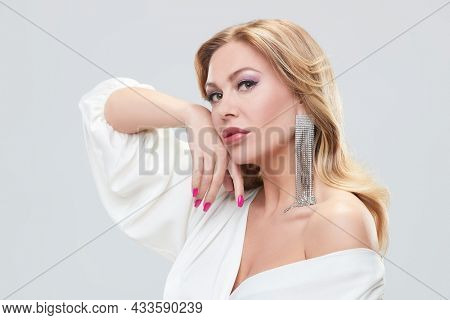 Beautiful sexy middle aged woman with enlarged full lips and evening makeup posing in precious jewelry. Beauty and jewelry. White background.