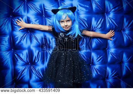 Lovely smiling little girl wearing a black kitty costume with a bright blue wig and cat ears. Joy at a Halloween costume party. Carnival kitty costume. Blue background.