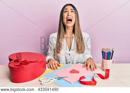 Young hispanic woman making valentine gift sitting on the table angry and mad screaming frustrated and furious, shouting with anger. rage and aggressive concept.