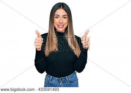 Young hispanic woman wearing casual clothes success sign doing positive gesture with hand, thumbs up smiling and happy. cheerful expression and winner gesture.