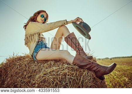 Full length portrait of a romantic girl sitting on a haystack in a field under the rays of the setting sun. Modern hippie style. Summer and autumn fashion.