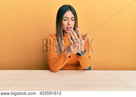 Young hispanic woman wearing casual clothes sitting on the table suffering pain on hands and fingers, arthritis inflammation