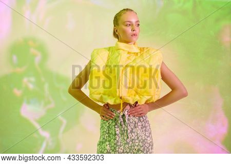 Fashion shot. Portrait of a stylish girl posing at studio in fashionable summer clothes on a light green background. Bright summer style.