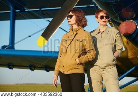 Aviation. Two professional female commercial aviation pilots in uniform and sunglasses stand in front of their plane at the airfield.