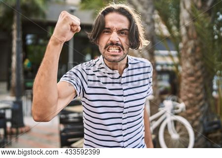 Young hispanic man with beard outdoors at the city angry and mad raising fist frustrated and furious while shouting with anger. rage and aggressive concept.