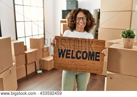Middle age hispanic woman smiling confident holding welcome doormat at new home